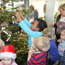 Kindergartenkinder schmücken den Weihnachtsbaum im Bürgerbüro